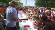 MS PAN Shot of children competing at watermelon eating contest during World Championship Cardboard Boat Race / Heber Springs, Arkansas, United States