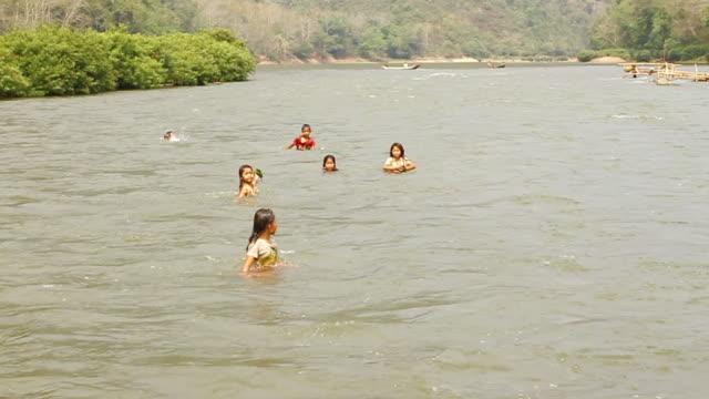 MS ZI SLO MO Shot of children swimming in river / Ou river, Luang Prabang, Laos