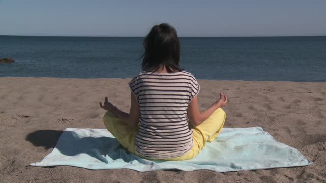 Shot of Chinese Woman practicing Yoga on the beach