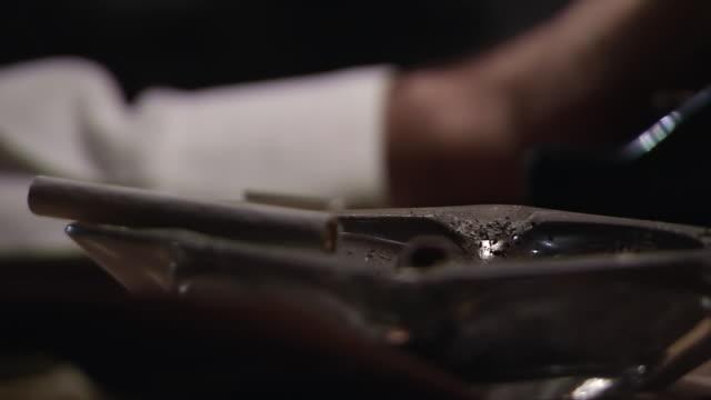 ECU Shot of Cigarette in ashtray on desk as man types in back side / United States