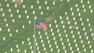 MS AERIAL Shot of Circling US flag at Jefferson Barracks Cemetery with graves in back side / St Louis, Missouri, United States
