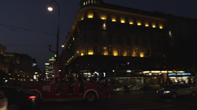MS PAN Shot of city at night with bus passing on street / Vienna, Austria