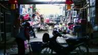 MS SLO MO Shot of closing of small store at night and woman sweeping floor / Luang Prabang, Laos