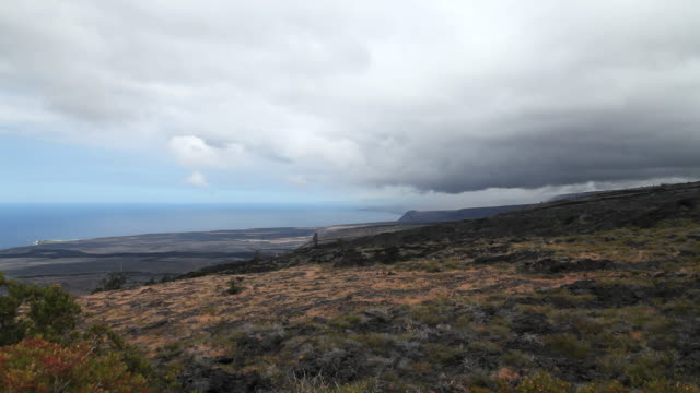 MS T/L Shot of clouds moving over field on side of volcano in Volcanoes National Park / Volcano, Hawaii, Big Island, United States