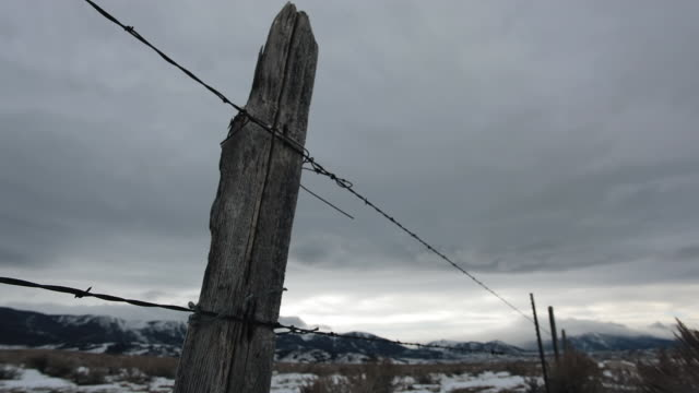 CU TL LA Shot of Clouds passing over barbed wire fence / Red Lodge, Montana United, States