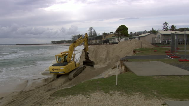 MS PAN Shot of Compound to excavator digging near sandbag / Kingscliff, New South Wales, Australia