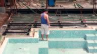 MS Shot of construction worker hosing down swimming pool area in construction zone / Montezuma, Punteranes, Costa Rica