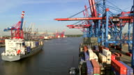 MS Shot of container ship with right side unloading containers in container ship on container terminal in harbour / Hamburg, Germany