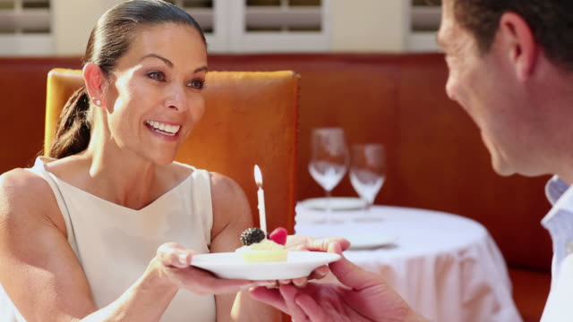 CU PAN Shot of couple blowing out candle in restaurant / Santa Fe, New Mexico, United States