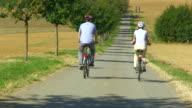 MS TU Shot of couple enjoying cycling with bikes and helmets on bikeway along river / Merzig, Saarland, Germany