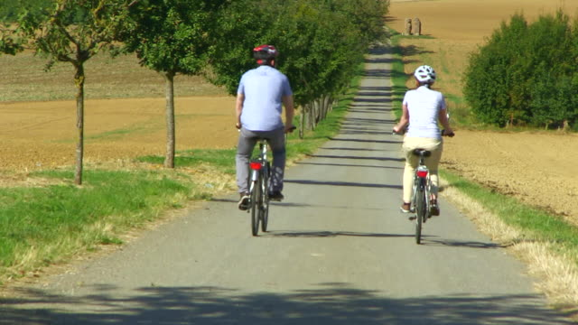 MS TU Shot of couple enjoying cycling with bikes and helmets on bikeway along river / Merzig, Saarland, Germany