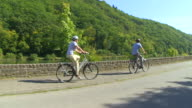 MS POV Shot of couple enjoying cycling with bikes and helmets on bikeway along river / Merzig, Saarland, Germany