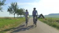 MS POV Shot of couple enjoying cycling with bikes and helmets through farmfield / Merzig, Saarland, Germany