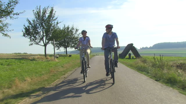 MS POV Shot of couple enjoying cycling with bikes and helmets through farmfield / Merzig, Saarland, Germany