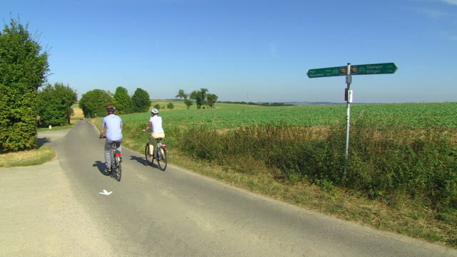 MS TU Shot of couple enjoying cycling with bikes and helmets through farmfield / Merzig, Saarland, Germany