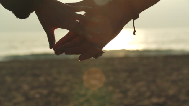 ECU SLO MO R/F Shot of couple holding hands on beach at sunset / Venice, California, United States