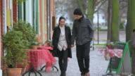WS TS Shot of Couple holding hands, walking happily along street in Dutch quarter in Potsdam / Potsdam, Brandenburg, Germany