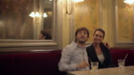 CU Shot of Couple sitting at table in restaurant with man beckoning waiter / Toulouse, Haute Garonne, France
