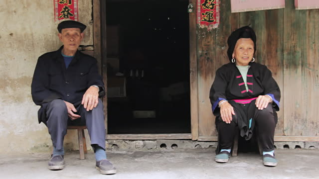 MS Shot of Couple sitting outside of house / Yao Village, Huangluo, China