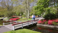 WS Shot of couple walking over bridge at Keukenhof Gardens / Lisse, South Holland, Netherlands