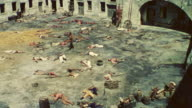 WS Shot of courtyard of a fortress with dead men on ground and a group of men with guns