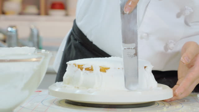 Shot of covering cake bread with cream