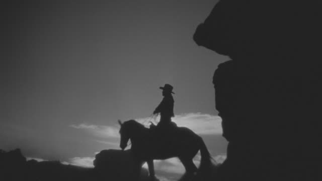 MS Shot of cowboys on horseback ride up on hill