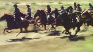 MS TS Shot of cowboys riding fast on horseback through  desert