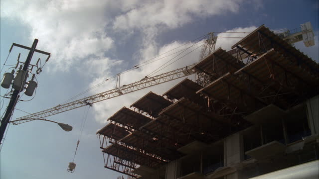 MS Shot of crane in motion at construction site at construction site