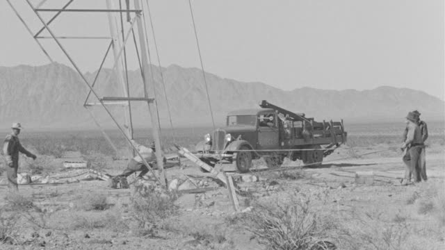 MS TU Shot of crew of men working on electrical tower in desert