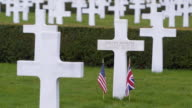MS PAN Shot of crosses stops at the grave of leland Simmons marked by American and British flags at the Cambridge American cemetery and memorial / Coton, Cambridgeshire, United Kingdom