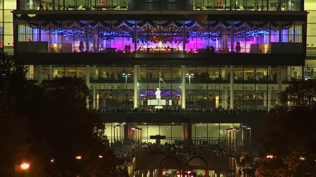 MS T/L Shot of Crowds arriving into Wembley Stadium at night / London, United Kingdom