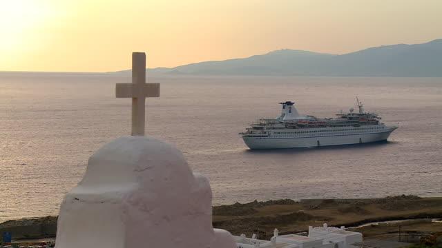 WS Shot of cruise ship with Aegean sea and church cross / Mykonos, Cyclades, Greece
