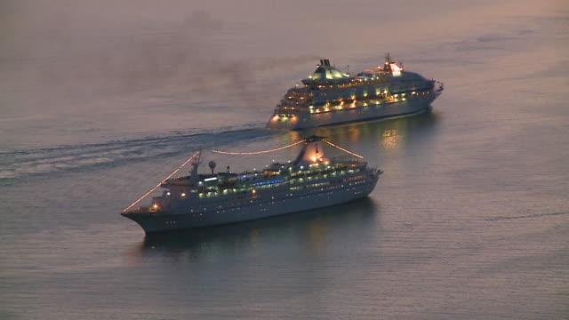 MS Shot of cruise ships in Caldera of Santorini at Sun setting / Santorini, Cyclades, Greece