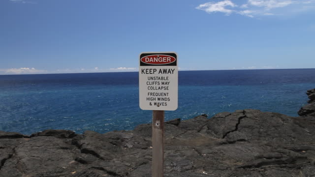 MS PAN Shot of danger sign on volcanic cliff edge in Volcanoes National Park with ocean / Volcano, Hawaii, Big Island, United States