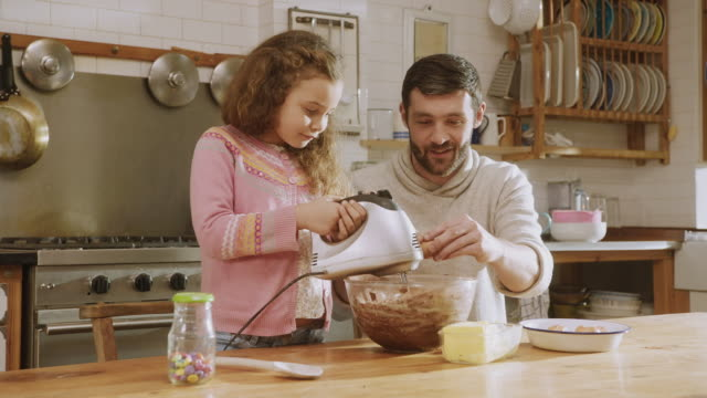 MS Shot of Daughter whisks cake mix as daddy holds and turns bowl / London, United Kingdom