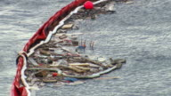 MS Shot of Debris from Costa Concordia within floating containment barrier / Giglio Porto, Tuscany, Italy