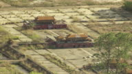 MS AERIAL Shot of decrepit buildings covered in graffiti and overgrown plants at Splendid China / Kissimmee, Florida, United States