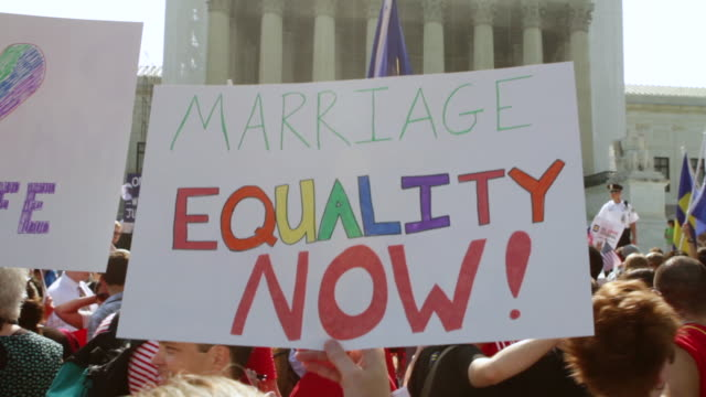 MS LA PAN Shot of demonstrators holding out signs in favor of marriage equality during rally in front of Supreme Court building / Washington, District of Columbia, United States