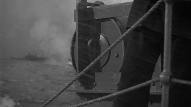 CU Shot of depth charge in rack being released into ocean at Large ships