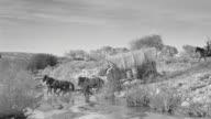 WS PAN Shot of desert to follow wagon train traveling through riverbed