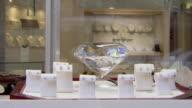 CU Shot of Diamond earrings on display on models in store window as people walking / Philadelphia, Pennsylvania, United States