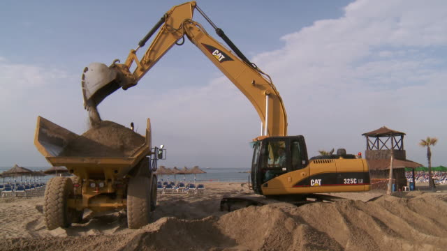 MS Shot of digging machine loading sand in truck to restored public beach / Marbella, Andalusia, Spain