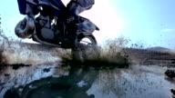 MS SLO MO Shot of dirt bike riding through puddle and splashing mud / Venice, California, United States