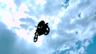 MS SLO MO LA Shot of dirt biker riding and jumping with hand stand and legs up in air / Venice, California, United States