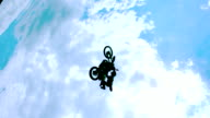 MS SLO MO LA DS Shot of dirt biker riding and jumping with legs in air / Venice, California, United States