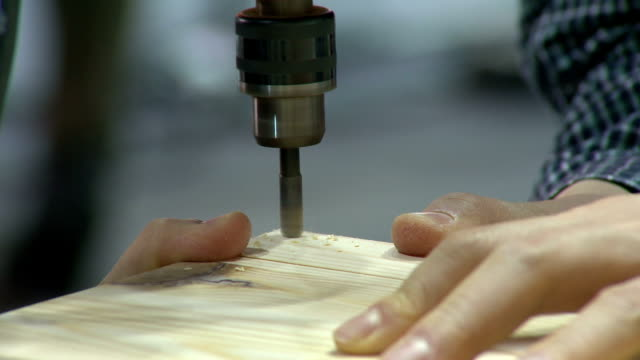Shot of drilling plywood and driving a screw with drill