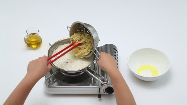CU Shot of dropping pasta noodles into boiler and mixing to make pasta / Seoul, South Korea