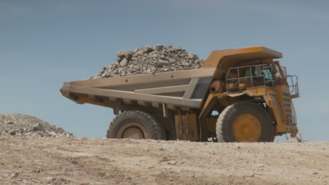 MS TS Shot of dump truck reversing with full load and then tipping load / Namibia