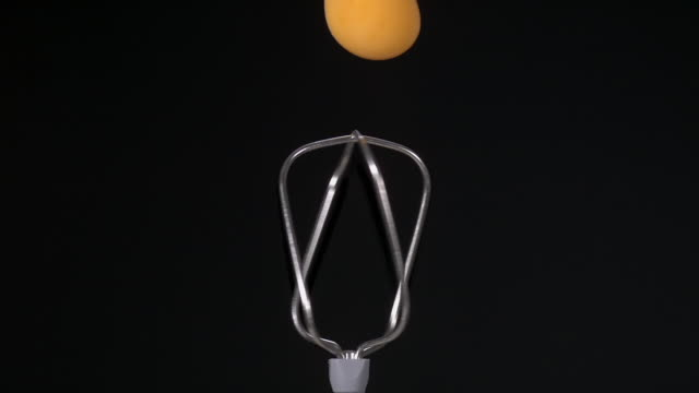 CU SLO MO Shot of egg yolk getting smashed while falling into spinning hand mixer / Munich, Bavaria, Germany